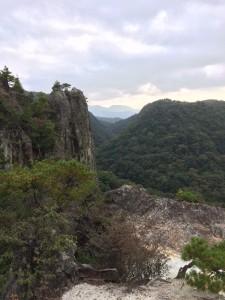 ロウソク岩。中央は鎌倉峡のV字谷。その向こうに六甲の山並み。